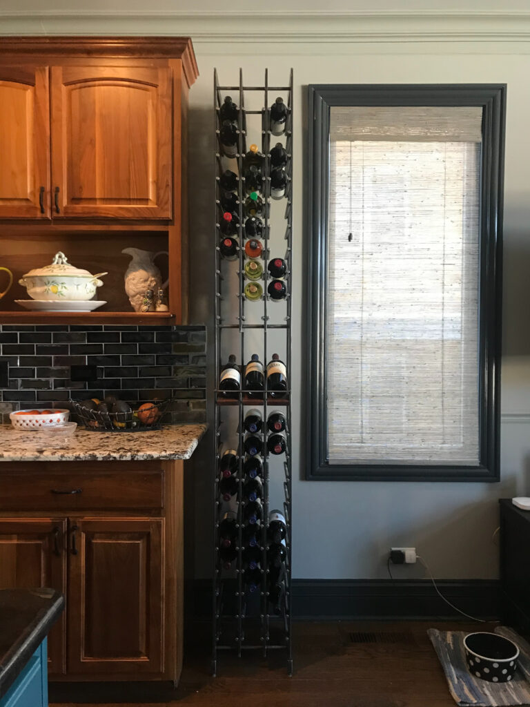 Tall wine rack between kitchen cabinets and a window
