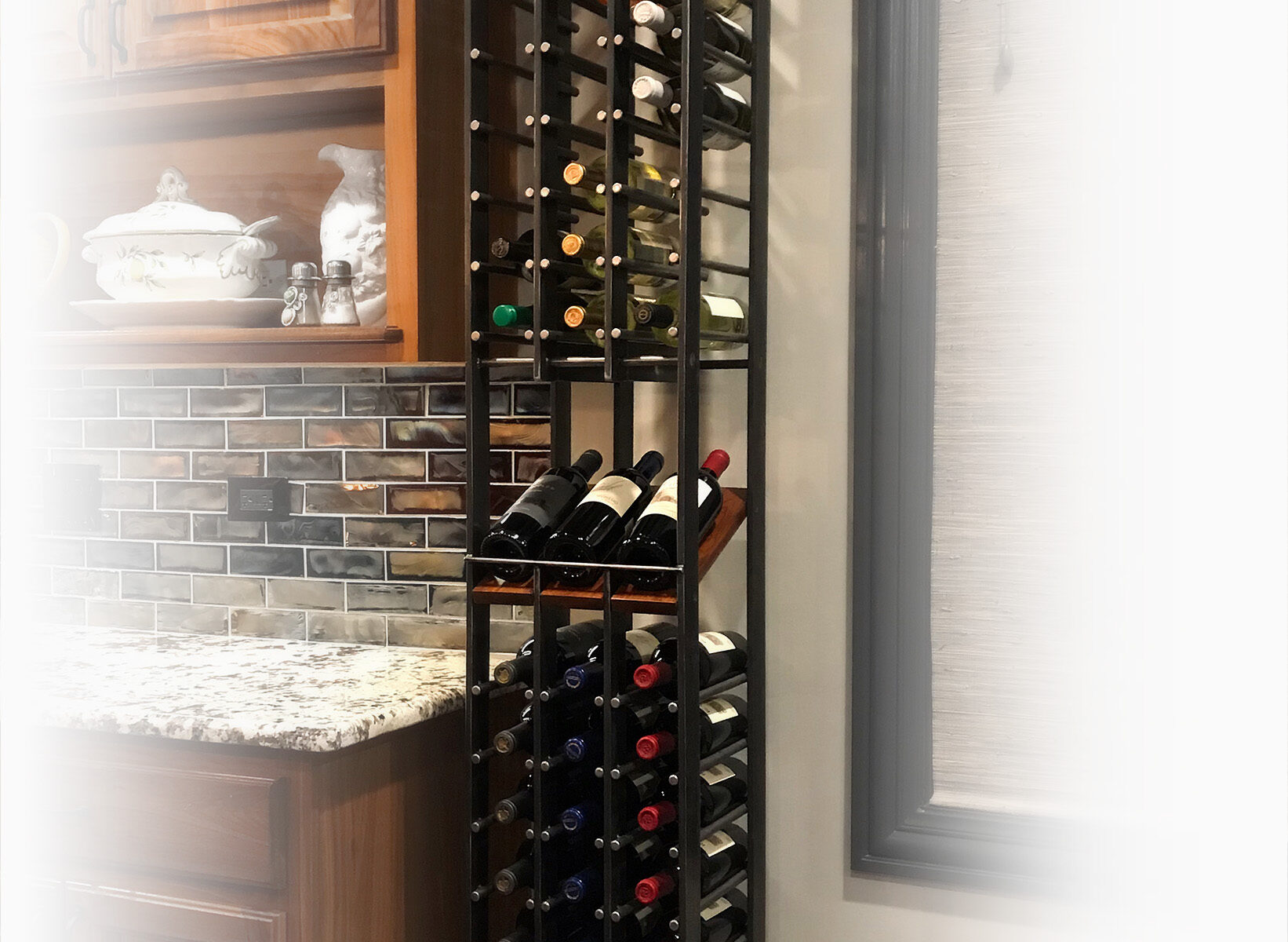 Tall wine rack between kitchen cabinets & a window
